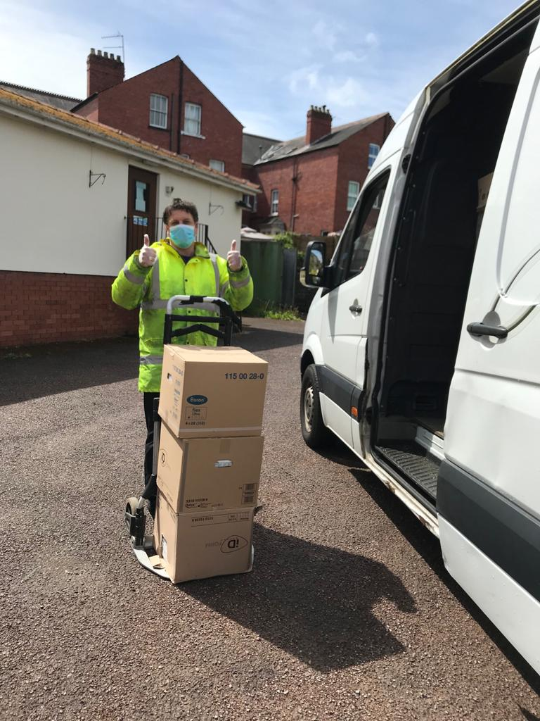A volunteer loading deliveries into a van